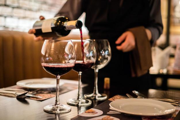 En mand hælder rødvin op i 2 glas på en restaurant