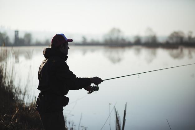 En mand der står og fisker