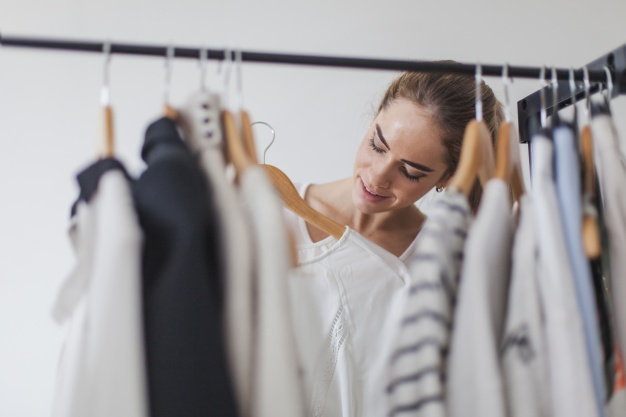 Kvinde kigger på tøj i garderobeskab