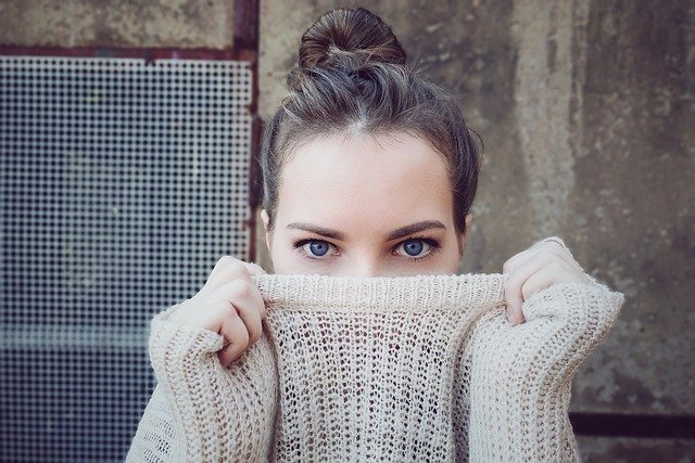 Kvinde holder en striktrøje over næsen