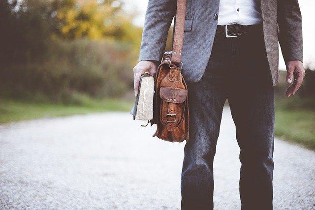 En mand i jakkesæt går på en vej med en bog i hånden